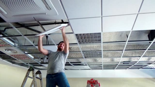 Construction worker performs a suspended ceiling maintenance with mineral fiber squares.