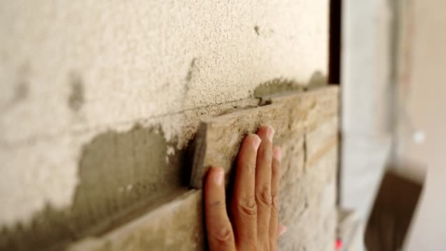 Construction worker puts a stone on the wall