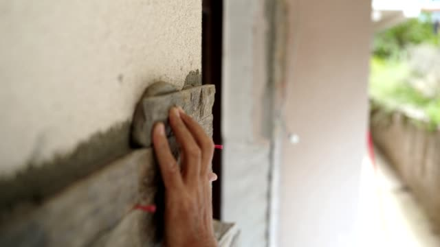 Construction worker puts a stone on the wall Construction worker is putting glue on a piece of stone and gluing it on the wall. house painter stock videos & royalty-free footage