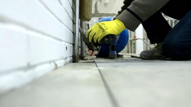 Construction worker puts ceramic tiles on the floor. video