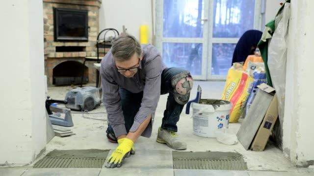 construction worker puts ceramic tiles on the floor. - imprenditore edile video stock e b–roll