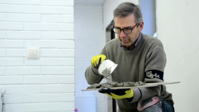Construction worker puts the building glue on the ceramic tile. video