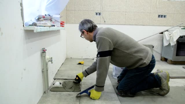 Construction worker puts the building glue on the floor. video