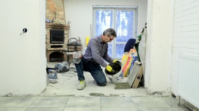 Construction worker puts the glue on the floor. video