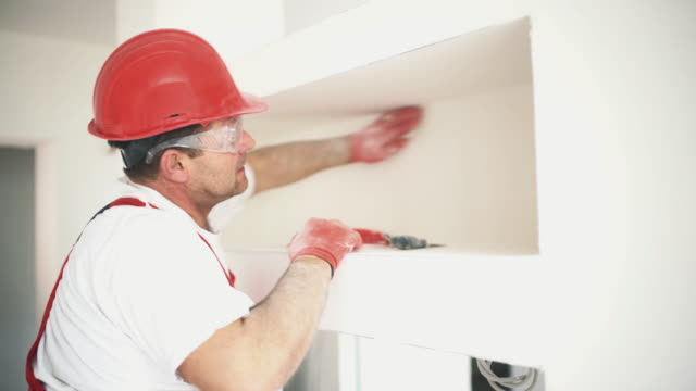 Construction worker sanding a drywall. Closeup side view of a construction worker sanding surface and edges of a newly built drywall and preparing it for painting. He's wearing a red uniform and a red helmet.  4k video house painter stock videos & royalty-free footage