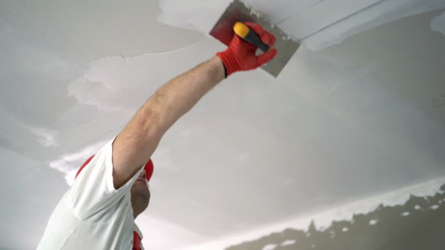 Construction worker sanding a drywall. Closeup low angle view of a construction worker finishing a sutface of a ceiling. He's applying some plaster with a trowel. He's wearing a red uniform and a red helmet.  4k video house painter stock videos & royalty-free footage