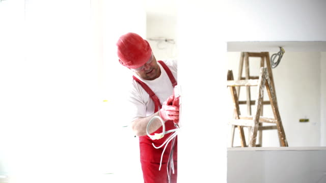 Construction worker sanding a drywall. Closeup side view of a partially unrecognizable construction worker sanding surface and edges of a newly built drywall and preparing it for painting. He's wearing a red uniform and a red helmet.  4k video house painter stock videos & royalty-free footage