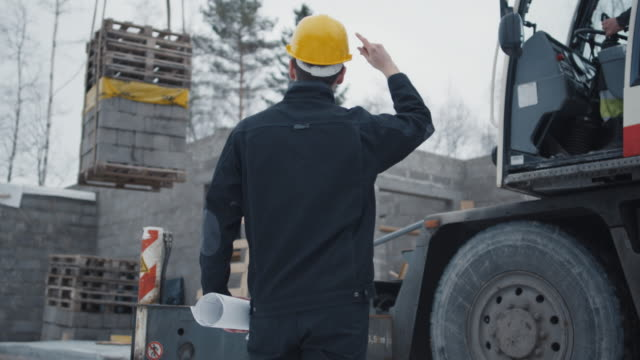 Construction Worker Signals to Crane Operator on Construction Site video