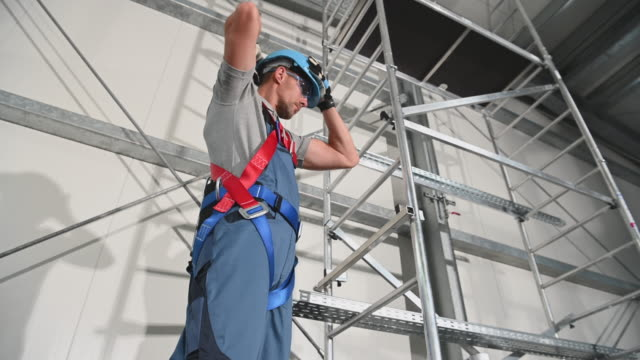 construction worker standing by scaffold putting on and adjusting hard hat - imbracatura video stock e b–roll