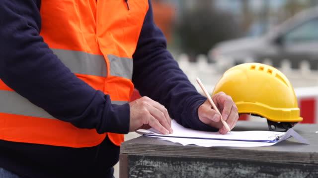 vidéos et rushes de ouvrier, prendre des notes sur chantier - inspecteur