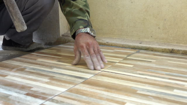 construction worker tiling ceramic tiles floor, dolly shot 4k video