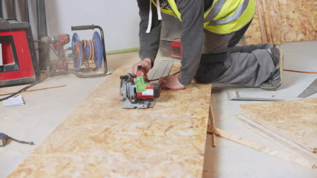 vídeos de stock e filmes b-roll de ds construction worker using a metal plank to help him cut the chipboard in a straight line - isolador