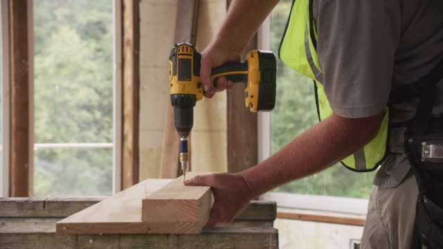 Construction worker using cordless screw gun Construction worker using cordless screw gun power tool stock videos & royalty-free footage