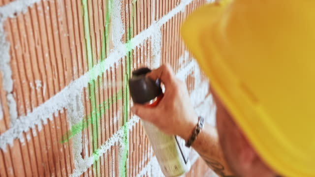Construction worker using spray paint to draw measurements on the wall