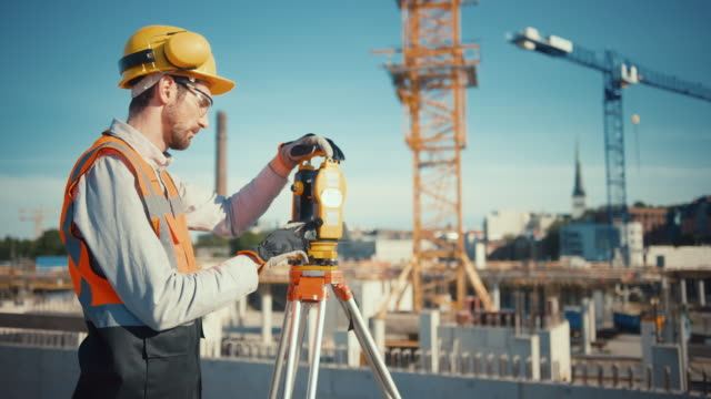 Construction Worker Using Theodolite Surveying Optical Instrument for Measuring Angles in Horizontal and Vertical Planes on Construction Site. Worker in Hard Hat Making Projections for the Building. Construction Worker Using Theodolite Surveying Optical Instrument for Measuring Angles in Horizontal and Vertical Planes on Construction Site. Worker in Hard Hat Making Projections for the Building. survey stock videos & royalty-free footage