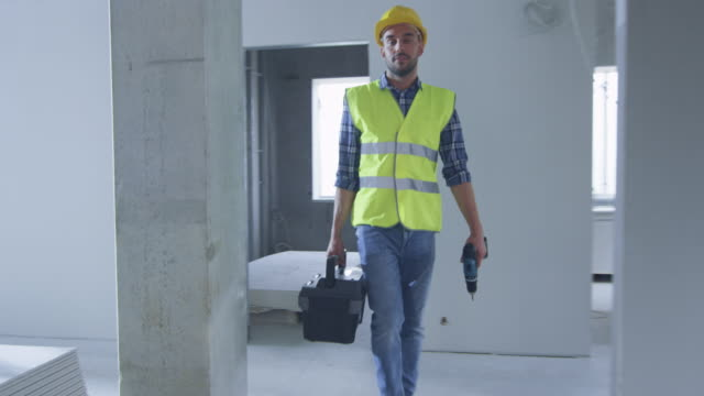 Construction Worker Walking inside Building Under Construction and Carrying Toolbox video