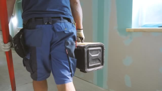 construction worker walking through the apartment with tool box and level in hands - tools filmów i materiałów b-roll