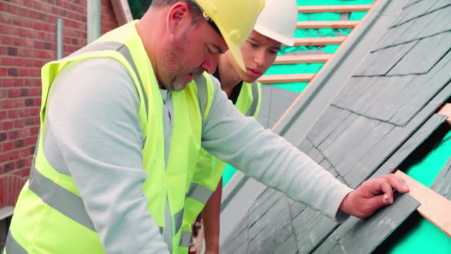 Construction Worker With Apprentice Laying Slate Tiles video