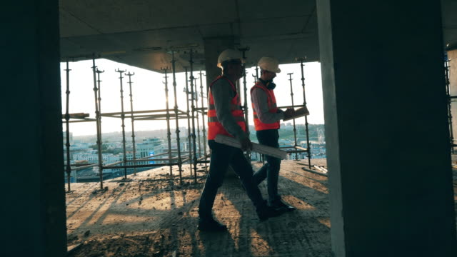 construction workers are walking along the building in progress - industria edile video stock e b–roll