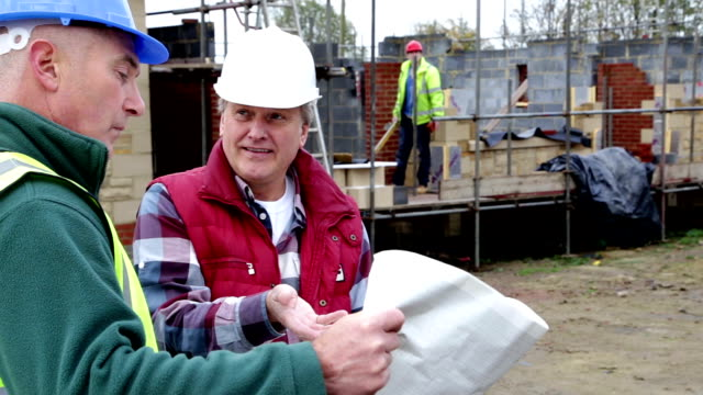 Construction Workers Discussing Plans on a Building Site video
