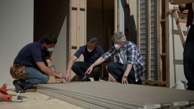 construction workers discussing something about the wall panels while measuring them on a sunny day - imprenditore edile video stock e b–roll