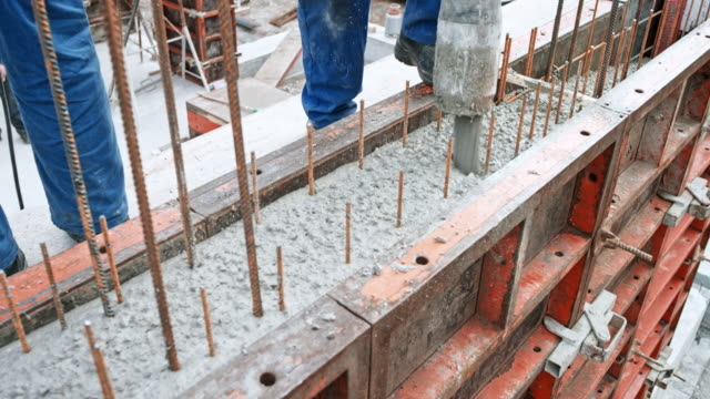 Construction workers filling formwork with concrete