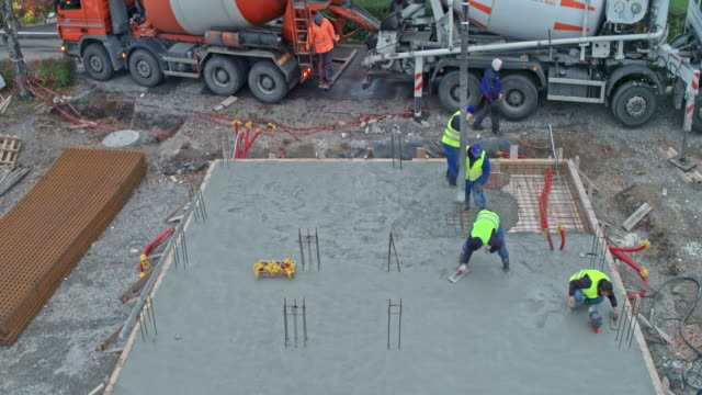 aerial construction workers finishing the foundation at the construction site - бетон стоковые видео и кадры b-roll