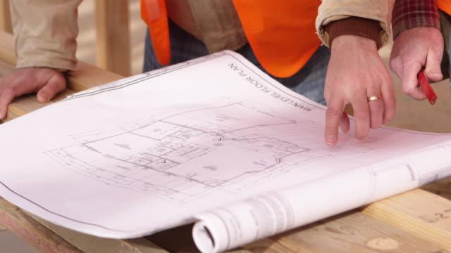 construction workers looking at house floor plans - osiedle mieszkaniowe filmów i materiałów b-roll