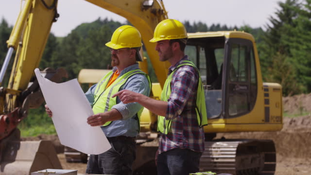 Construction workers looking at plans video