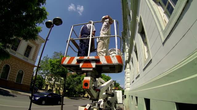 construction workers on hydraulic platform - skylift bildbanksvideor och videomaterial från bakom kulisserna