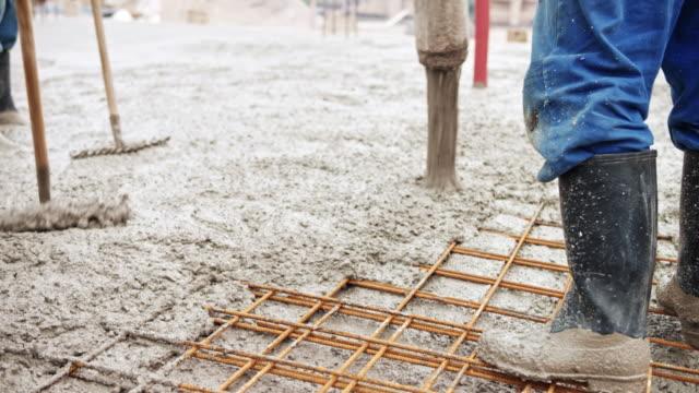 ワイヤー メッシュにわたってコンクリートを注ぐ建設労働者 - セメント点の映像素材/bロール