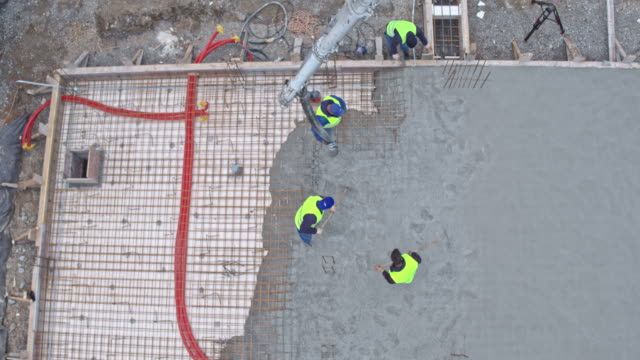 AERIAL Construction workers pouring concrete for the foundation