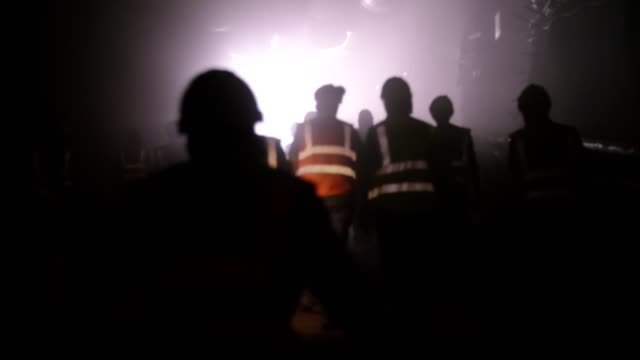 construction workers walking out from a dark smoke filled tunnel - sottosuolo video stock e b–roll