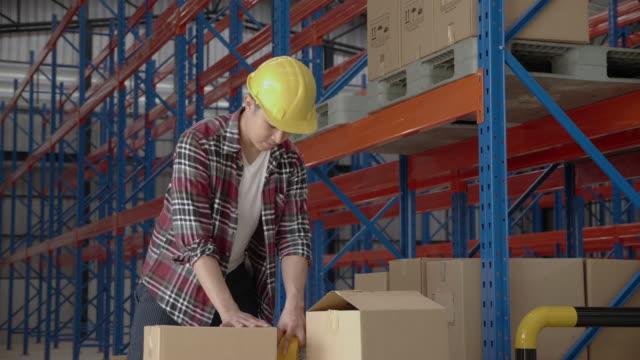 건설 노동자들은 온라인 배달을 위해 상자를 들어 올리기 위해 단단한 모자를 착용합니다. 공장, 컨테이너 또는 창고에서 작동합니다. 직장에서 사고를 방지하기 위한 안전 헬멧. 컨셉 물류 공� - 한 명의 중년 남자만 스톡 비디오 및 b-롤 화면