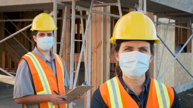 Construction workers wearing a protective face mask working at a construction site