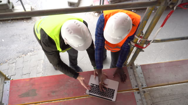 Construction workers with safety jackets looking at computer. View from above video