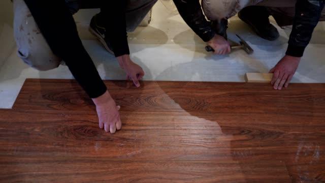 木製ラミネート床で作業建設労働者 ビデオ