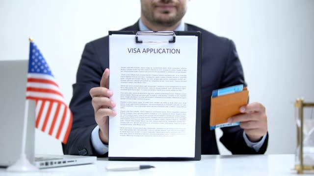 vídeos y material grabado en eventos de stock de oficial consular de ee.uu. que muestra la solicitud de visa y pasaporte, inmigración legal - pasaporte y visa
