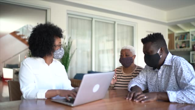 Consultant using laptop and face mask. She's giving advice to a couple at customer's house Consultant using laptop and face mask. She's giving advice to a couple at customer's house financial planning stock videos & royalty-free footage