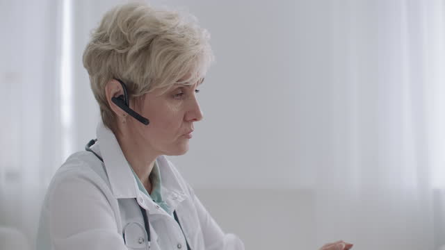 consultation of doctor by telephone, female physician is answering on questions of patients in call-center, profile view