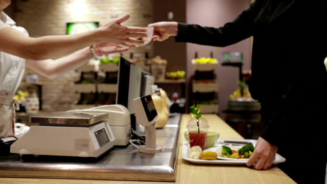 Contactless payment of lunch in cafeteria, handheld shot After cafeteria worker weighs businesswoman meal portion, she pays it using mobile phone, handheld shot cafeteria stock videos & royalty-free footage