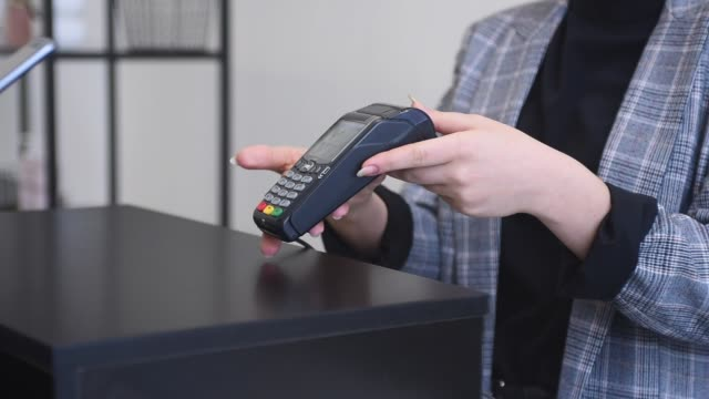 Contactless payment using her mobile phone. Smiling cashier accepting payment