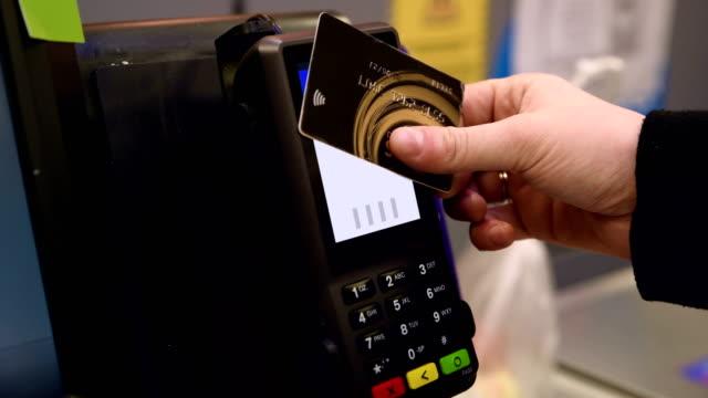 kontaktlös betalning med kreditkort i snabbköpet kassan-4k upplösning - spendera pengar bildbanksvideor och videomaterial från bakom kulisserna