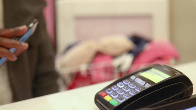 kontaktlös betalning med mobiltelefon i butik - köpnarkoman bildbanksvideor och videomaterial från bakom kulisserna