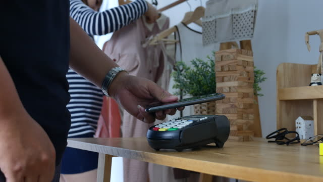 vídeos de stock e filmes b-roll de contactless payment with smart phone in store - paying with card contactless