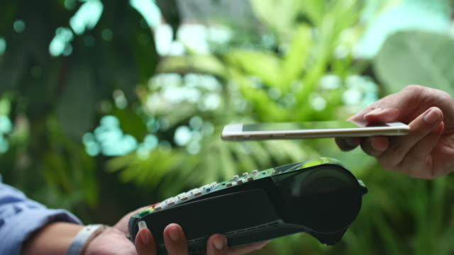 contactless payment with smart phone using nfc technology to pay - contactless payment stock videos & royalty-free footage