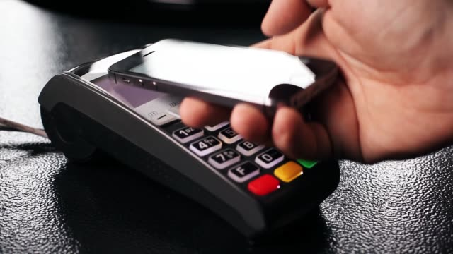 vídeos de stock e filmes b-roll de contactless payment with your smartphone. paying with a smartphone device on a credit card terminal. wireless payment - paying with card contactless