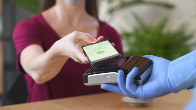 Contactless smartphone payment Close up hand of customer paying with smartphone. Cashier hand holding credit card reader machine and wearing protective disposable gloves at bar counter, while client holding phone for NFC payment. Woman wearing face mask while paying bill with mobile phone during Covid-19 pandemic. contactless payment stock videos & royalty-free footage
