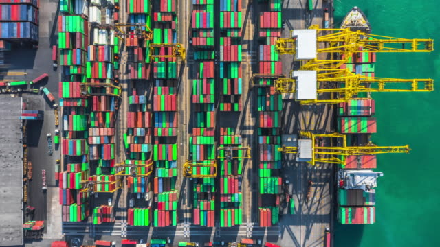 container cargo freight ship with working crane bridge discharge at container terminal, aerial top view container ship at deep sea port. - rotterdam video stock e b–roll