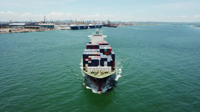 container cargo ship go out from harbor in ocean for export shipping - natante industriale video stock e b–roll